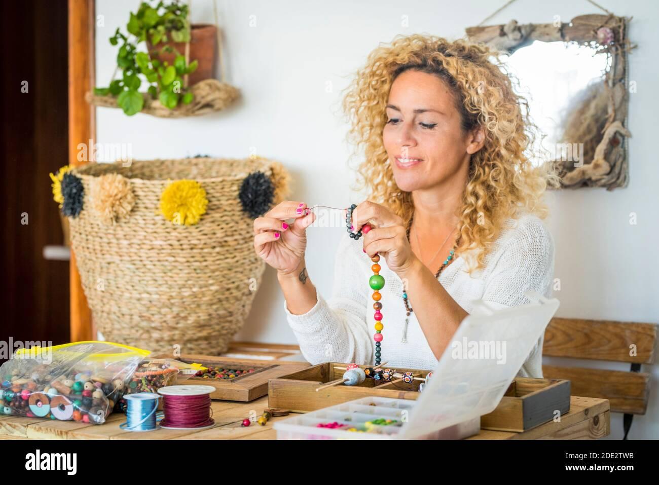 Femme joyeuse à la maison faisant des bracelets et colliers avec coloré perles - hobby art travail les gens le font soi-même concept - travail d'art pour les affaires en ligne Banque D'Images