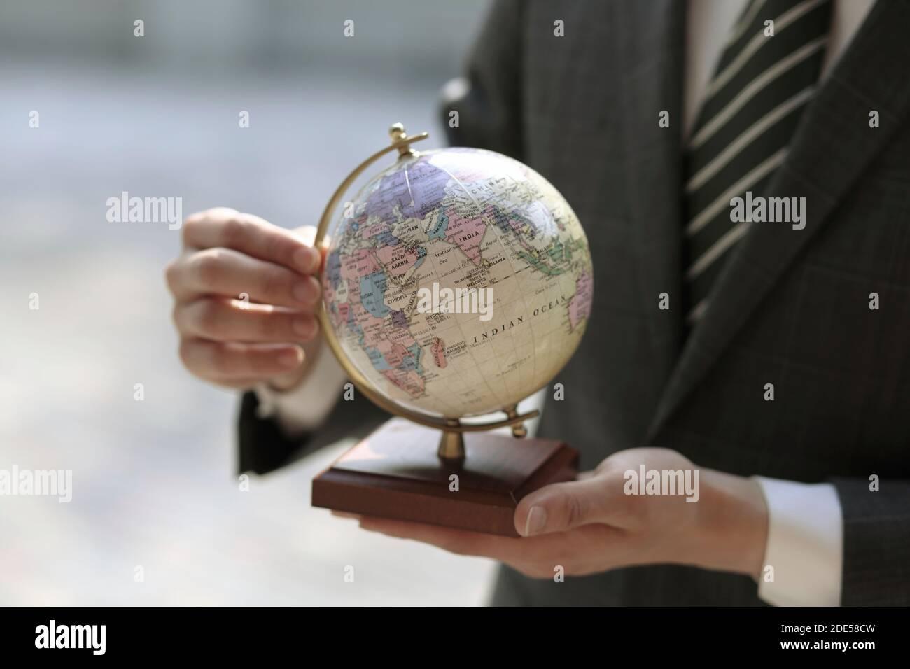 Gros plan sur un homme d'affaires tenant le globe Banque D'Images