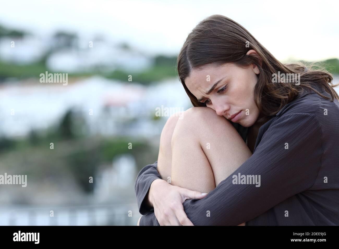 Triste adolescent assis seul se plaignant dans une ville côtière Banque D'Images
