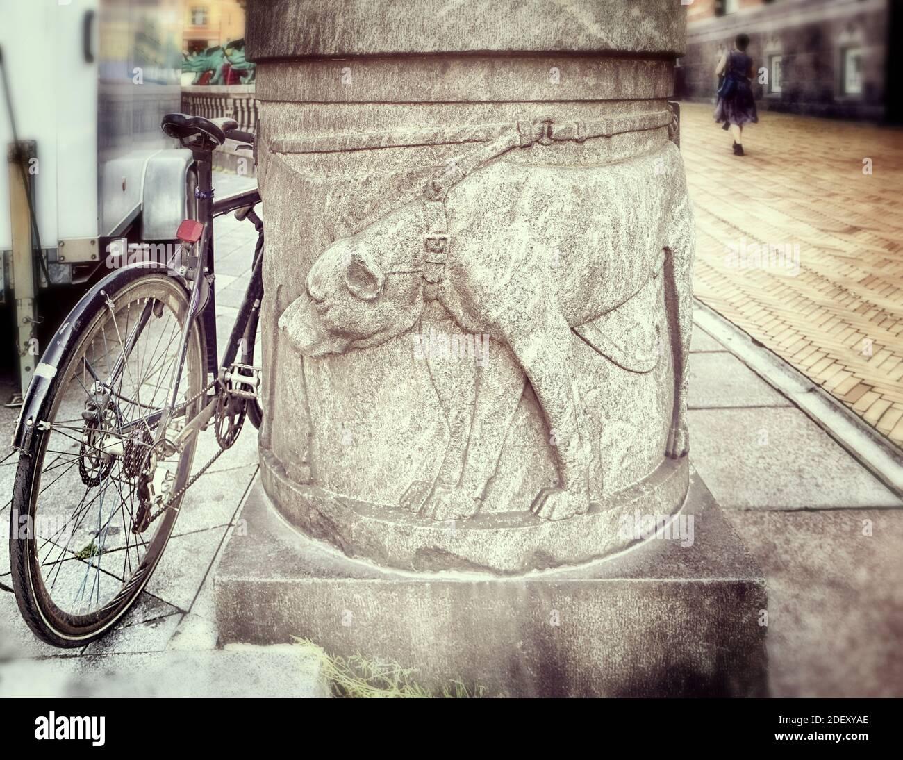 Un chien à collier sculpté à la base d'une colonne le long de la passerelle semble intéressé par une roue à vélo garée à proximité (pour prendre une fuite?), Copenhague Banque D'Images