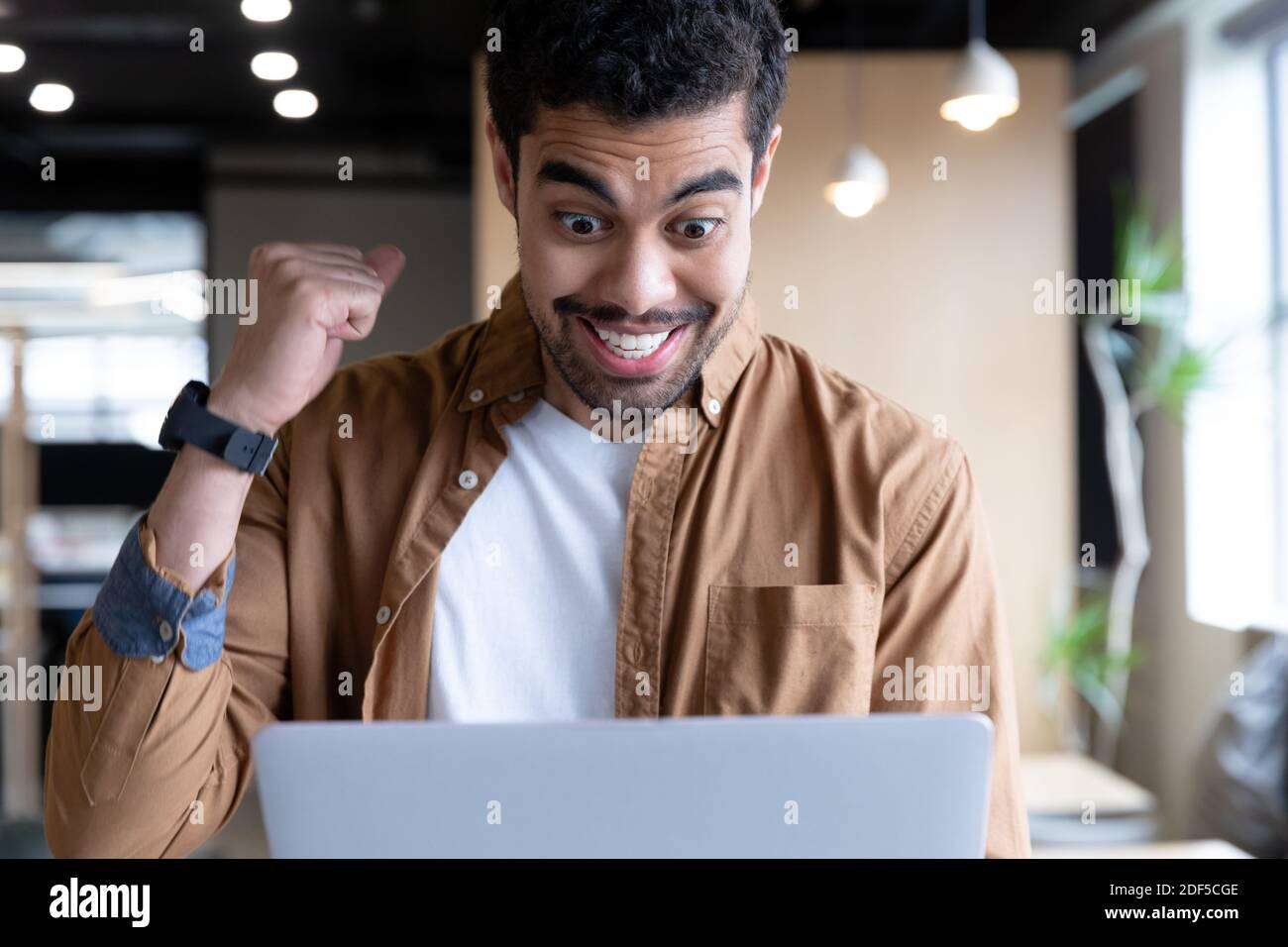 Applaudissent les hommes d'affaires de la course mixte utilisant un ordinateur portable lors d'un appel vidéo bureau Banque D'Images