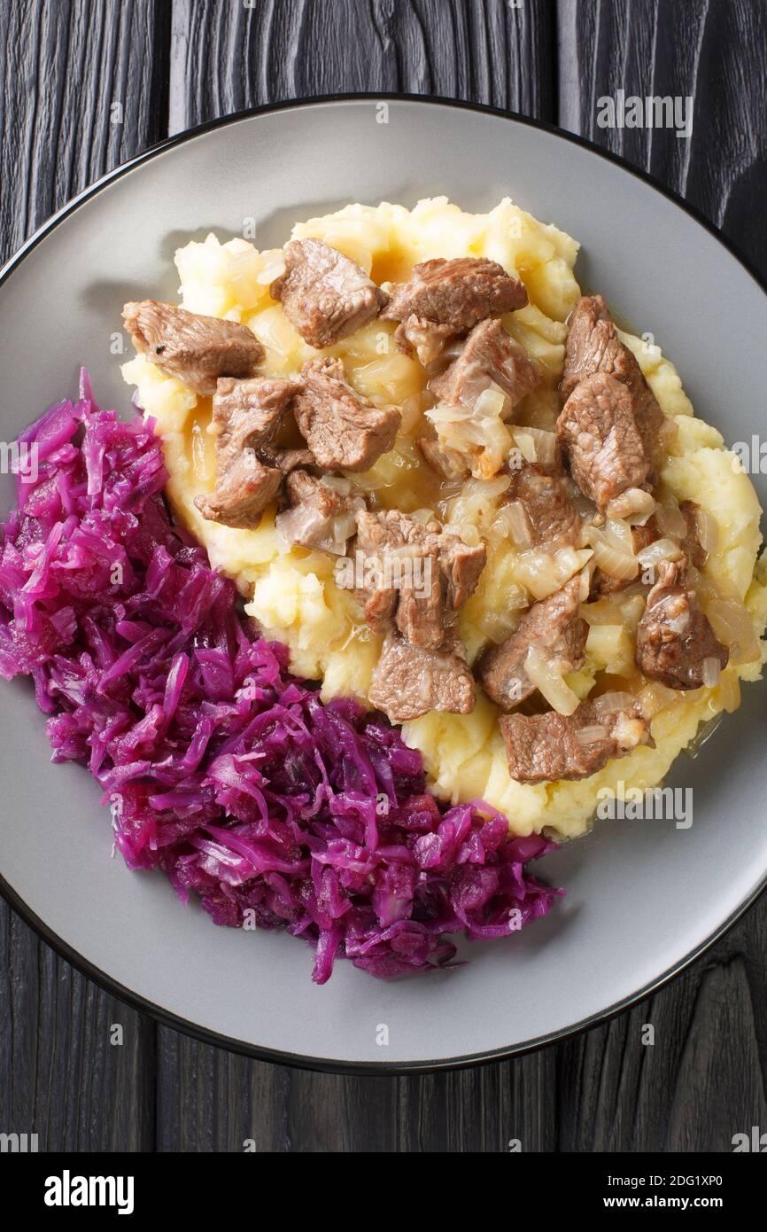 Ragoût de bœuf et d'oignon Hachee servi avec une purée de pommes de terre, un chou rouge braisé dans l'assiette sur la table. Vue verticale du dessus Banque D'Images