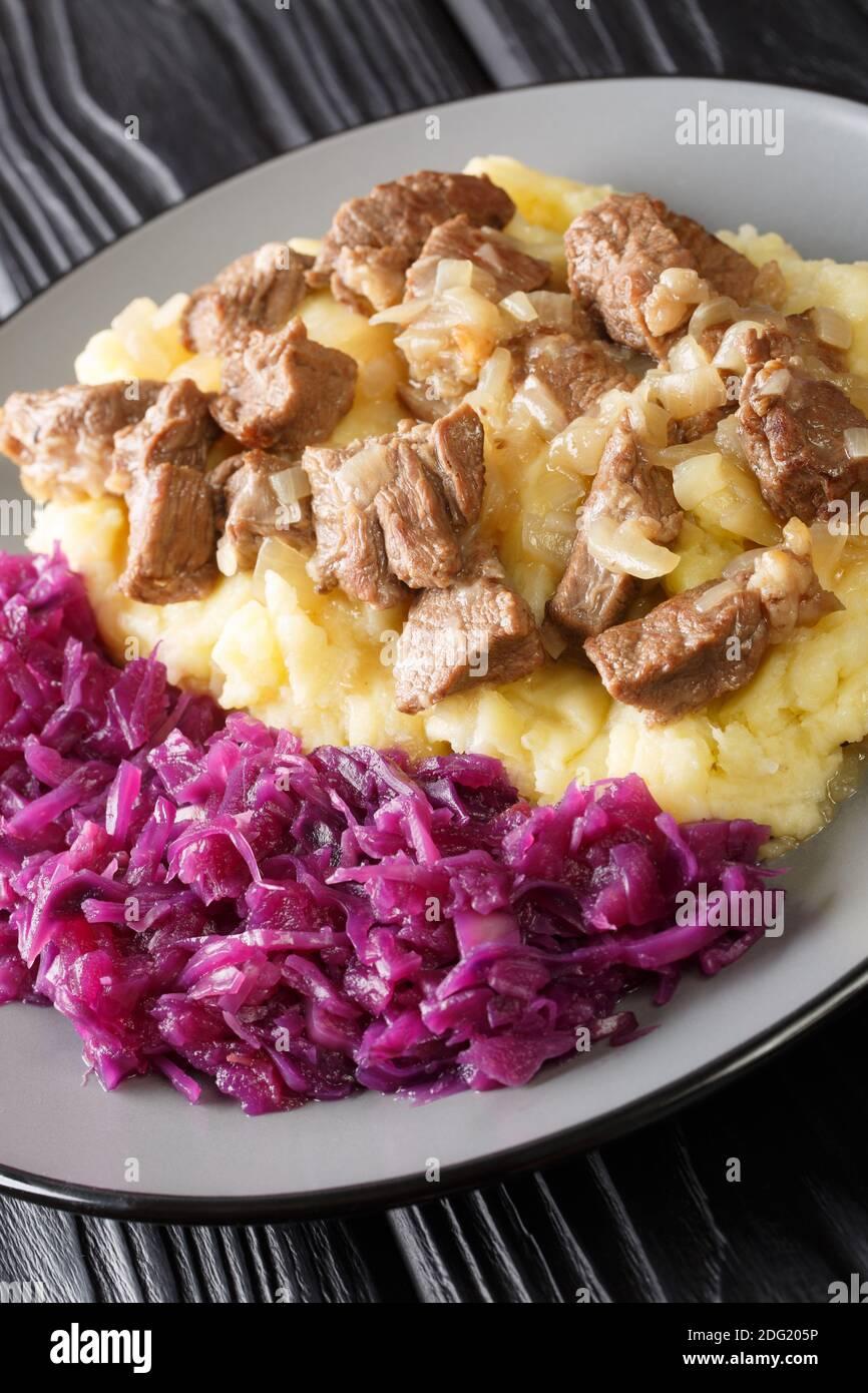 Ragoût de bœuf et d'oignon Hachee servi avec une purée de pommes de terre, le chou rouge braisé dans l'assiette sur la table. Vertical Banque D'Images