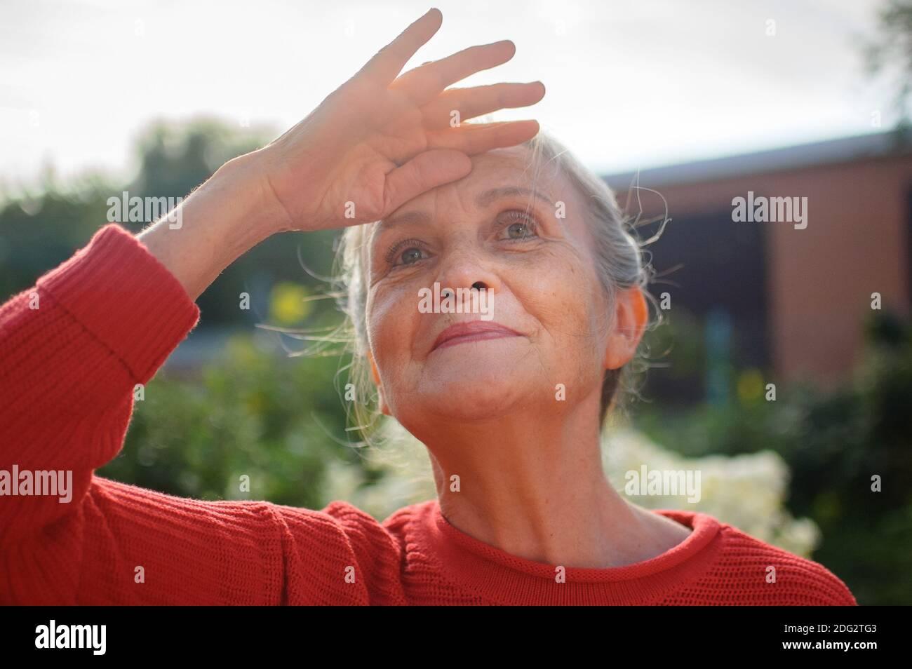 Portrait de femme âgée avec cheveux gris et visage avec des rides portant un chandail tricoté rouge et se détendent au parc pendant jour ensoleillé et à la recherche Banque D'Images