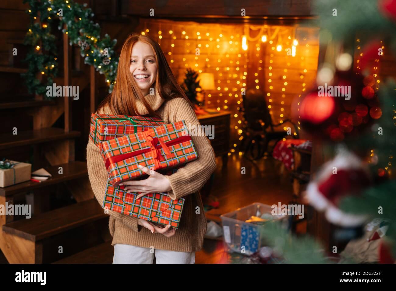 Portrait de jeune belle femme tenant une boîte avec des cadeaux de Noël enveloppés dans du papier artisanal. Banque D'Images