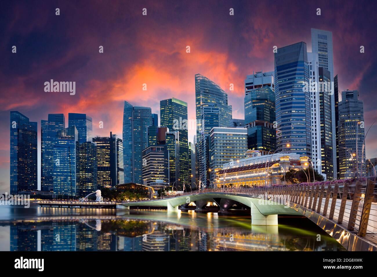 Vue imprenable sur le Merlion Park avec les gratte-ciel de Singapour en arrière-plan pendant un magnifique et spectaculaire coucher de soleil. Banque D'Images