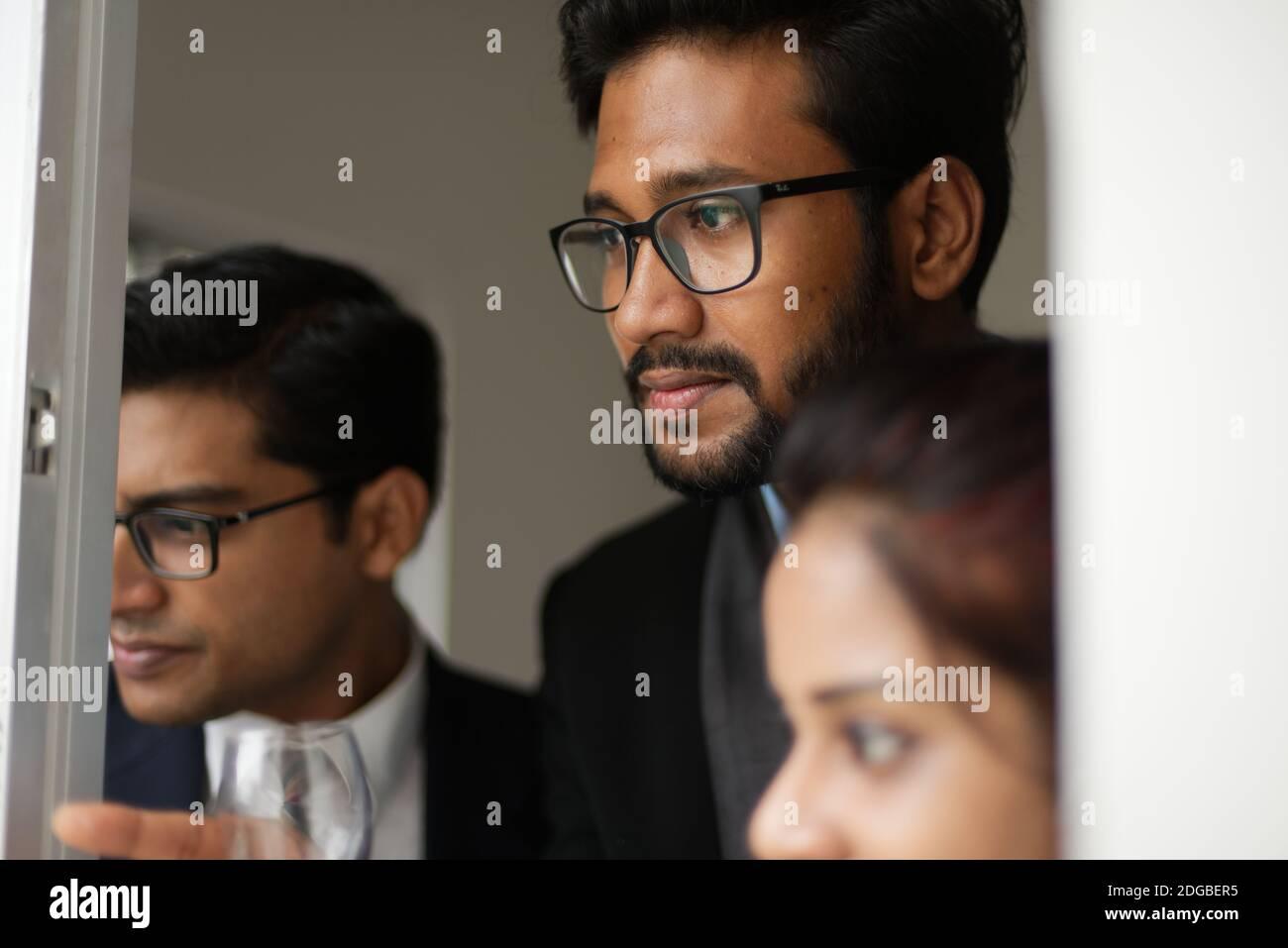 Réunions d'entreprise entre les jeunes et énergiques patrons/officiers/directeurs et secrétaire bengalis indiens à la fenêtre du bâtiment de bureau. Banque D'Images