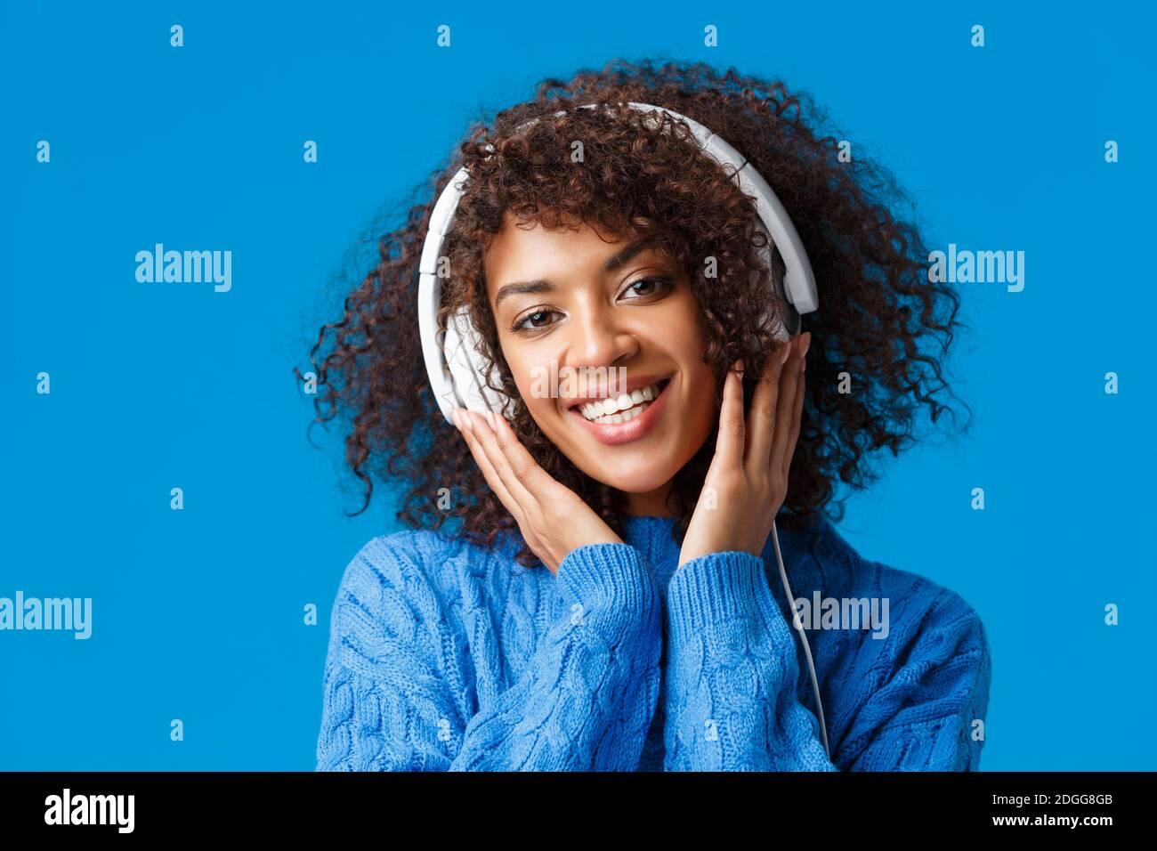 Portrait en gros plan taille basse femme afro-américaine attrayante avec une coiffure en forme de curly, mettre des écouteurs et sourire, écouter de la musique, Banque D'Images
