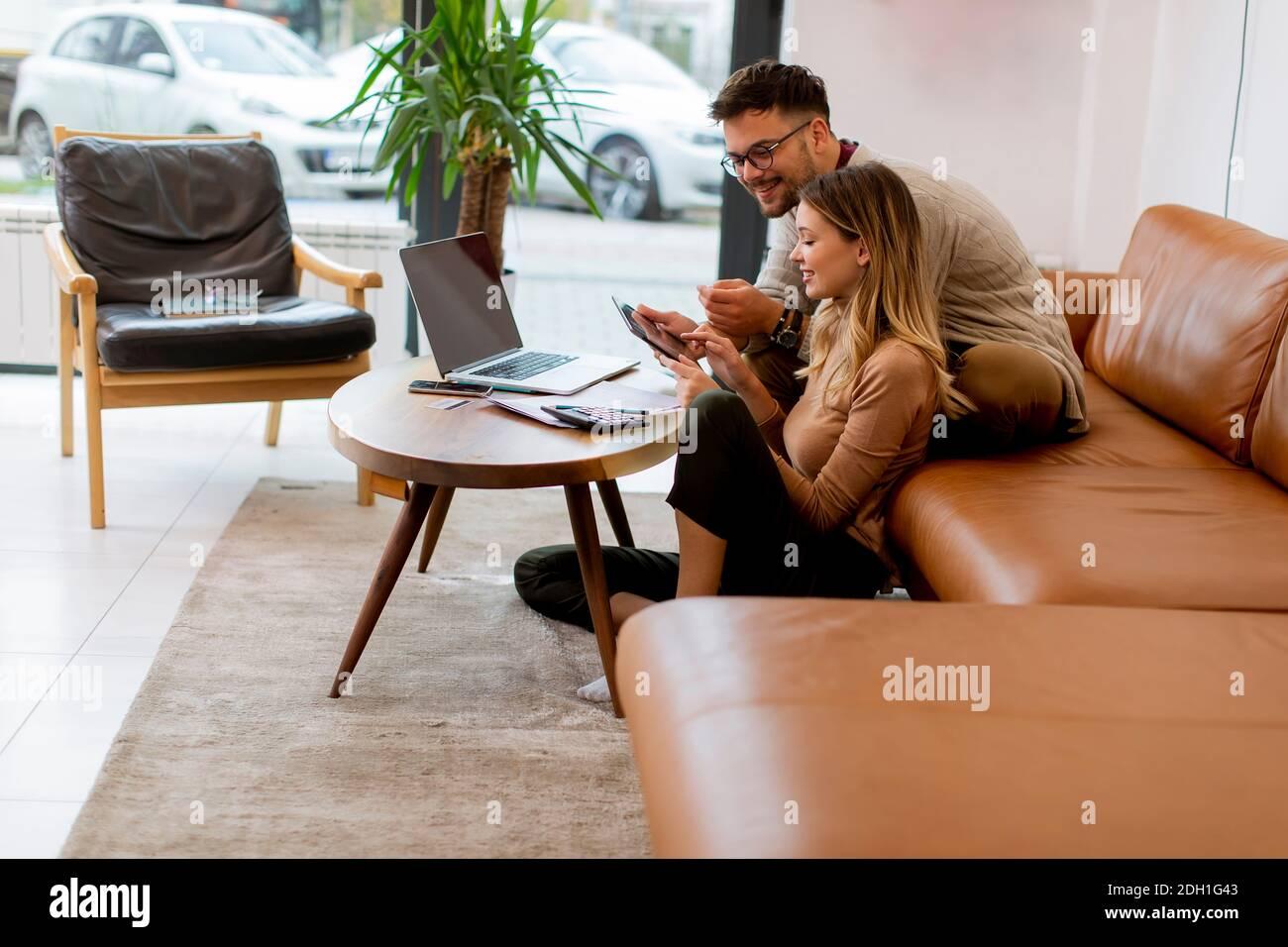 Beau jeune couple utilisant un ordinateur portable ensemble tout en étant assis sur un canapé à la maison Banque D'Images