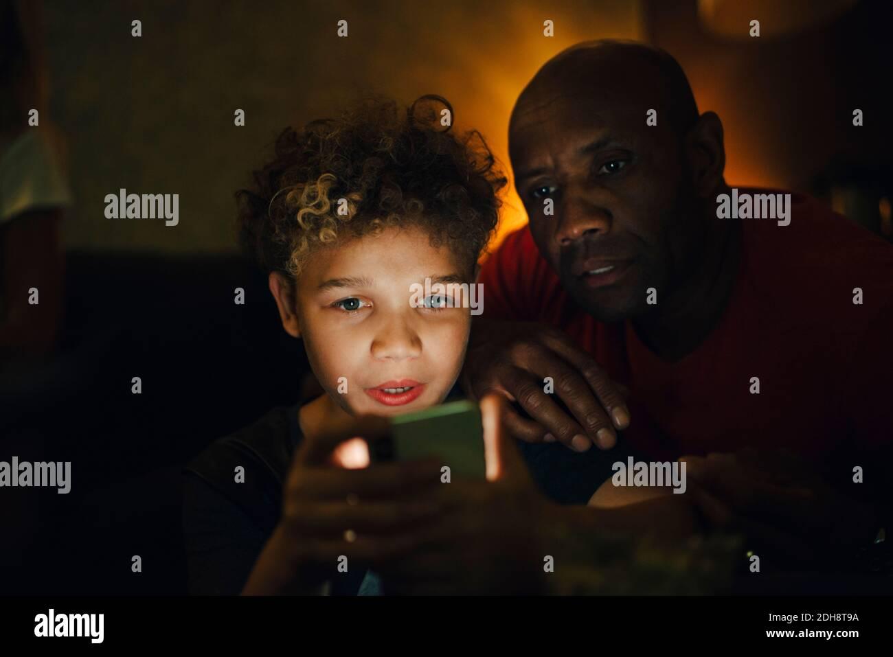 Garçon utilisant un smartphone par père dans le salon à nuit Banque D'Images