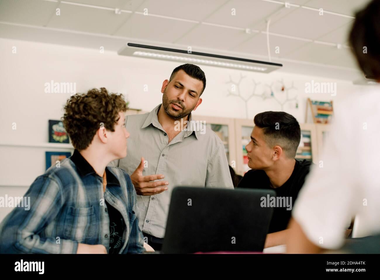 Professeur discutant avec des élèves de sexe masculin en classe Banque D'Images