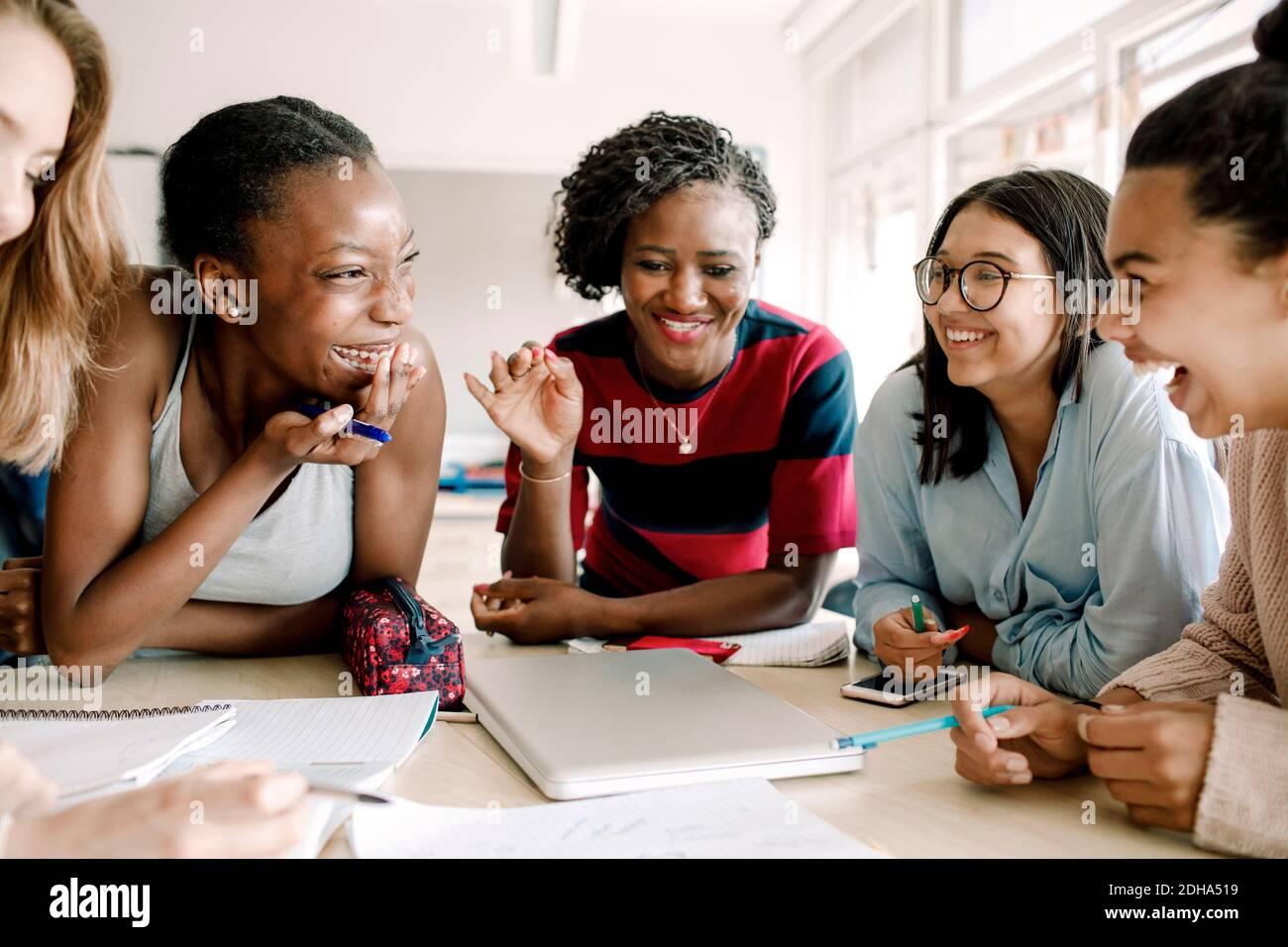Un professeur souriant se fait le gai pendant que des étudiants sont assis à table salle de classe Banque D'Images