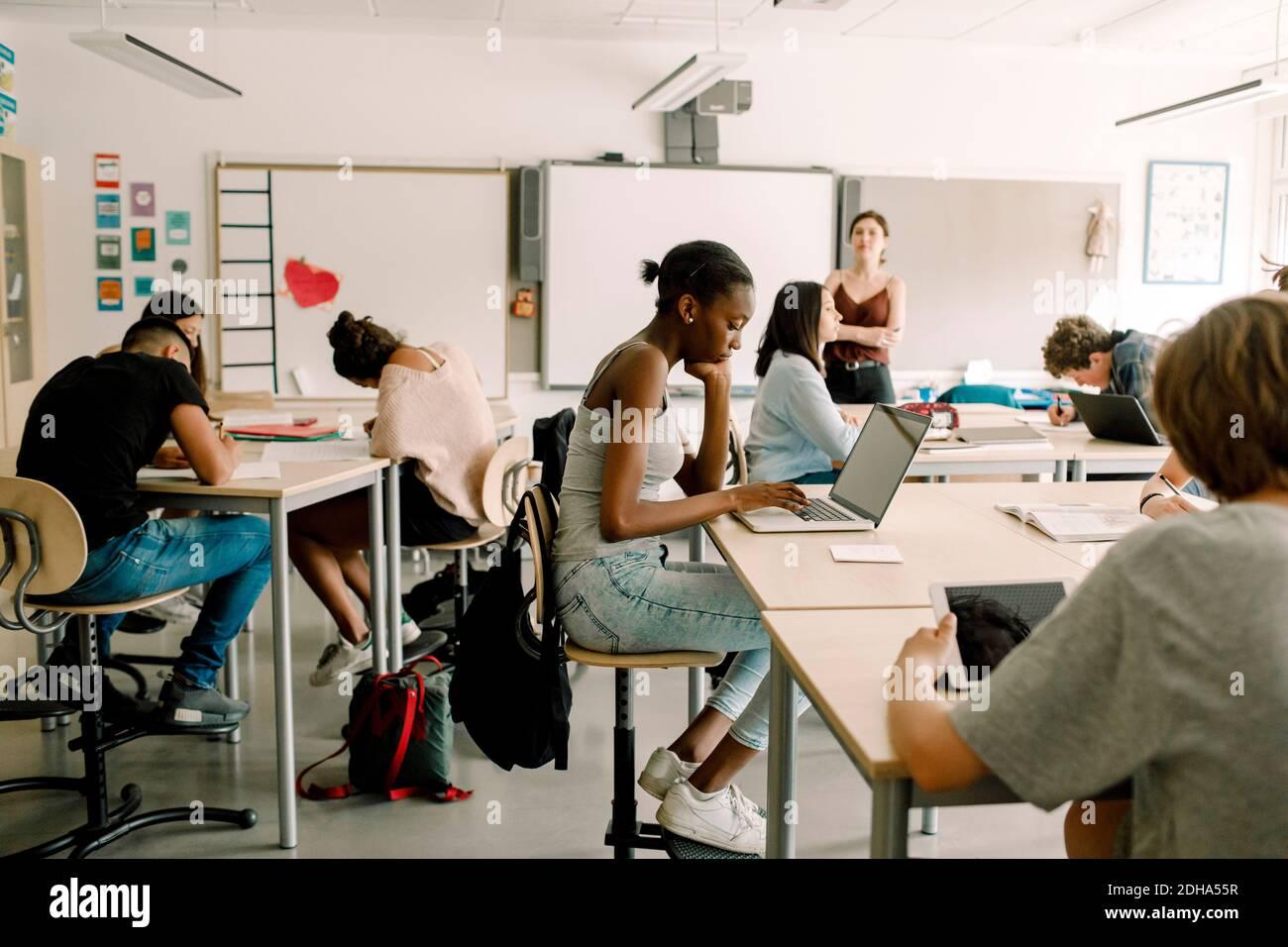 Étudiants de niveau secondaire junior étudiant pendant que la femme enseignant debout dans la salle de classe Banque D'Images