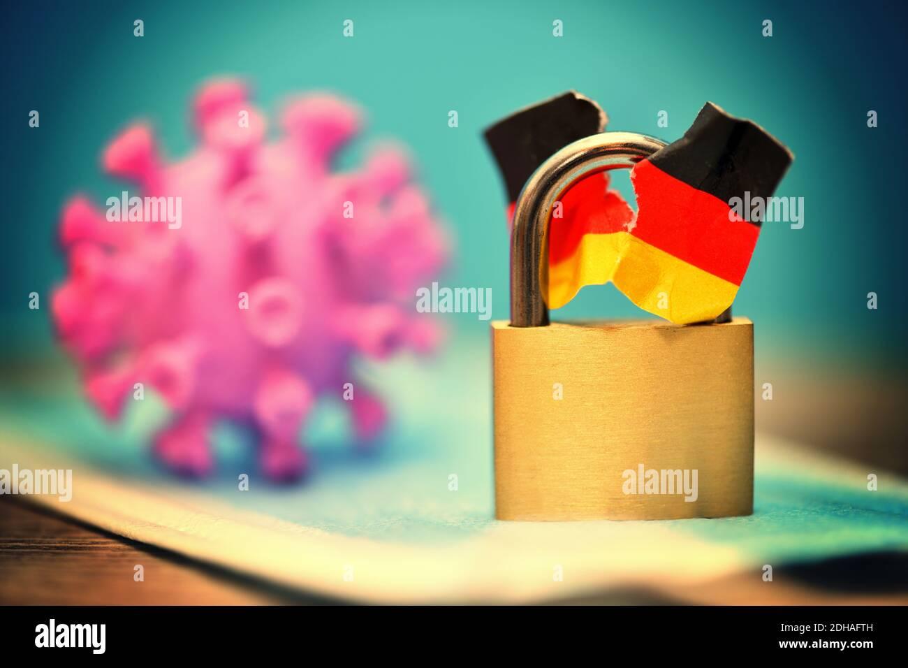 Geschlossenes Vorhängeschloss mit angerissener Deutschlandfahne und coronavirus, Spaltung der Gesellschaft durch den Lockdown Banque D'Images