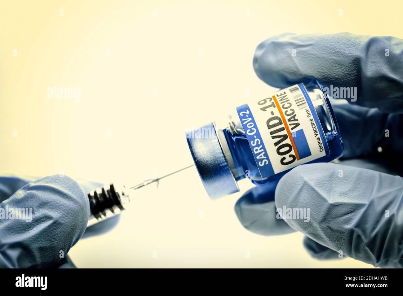 Hände in Zutzhandschuhen halten Injektionsfläschchen mit Corona-Impfstoff und Impfspritze, Symbolfoto Corona-Impfmittel Banque D'Images