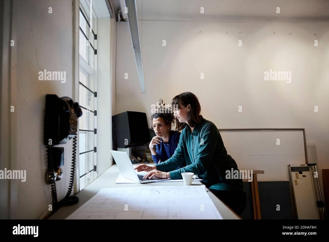 Femmes architectes discutant sur ordinateur portable à table au bureau Banque D'Images