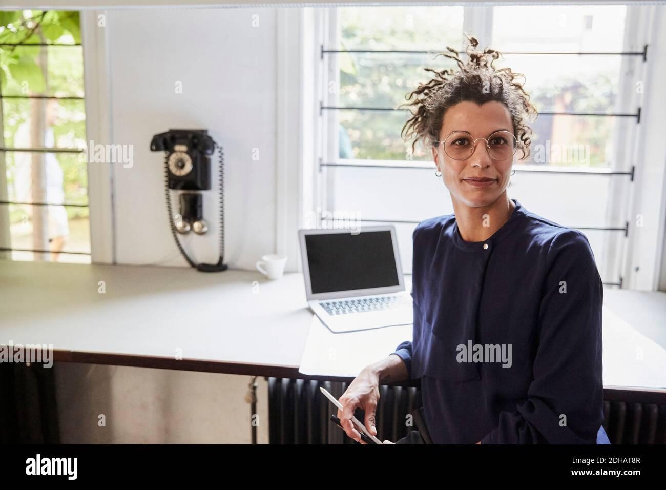 Portrait d'une femme architecte confiante assise à une table au bureau Banque D'Images