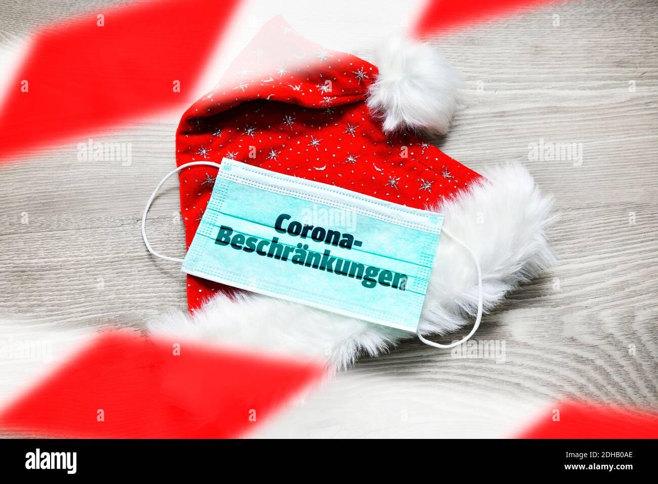 FOTOMONTAGE, Schutzmaske auf Weihnachtsmannmütze mit der Aufschrift Corona-Beschränkungen, Weihnachtsfest zu Corona-Zeiten Banque D'Images