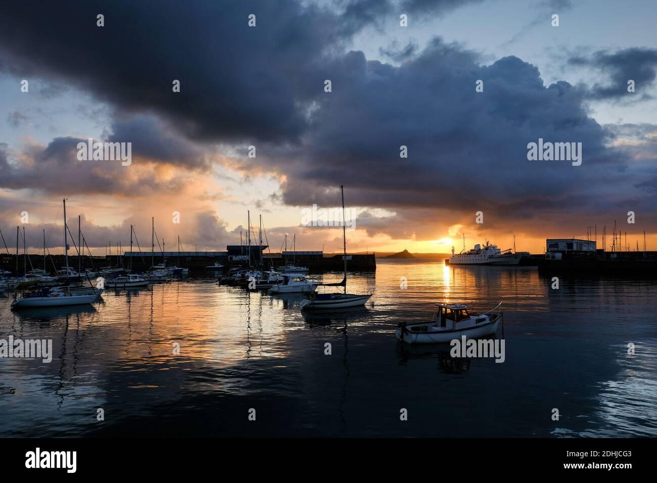 Le calme avant la tempête Alex, alors que le soleil se lève derrière le phare du port de Penzance le premier jour d'octobre. Banque D'Images