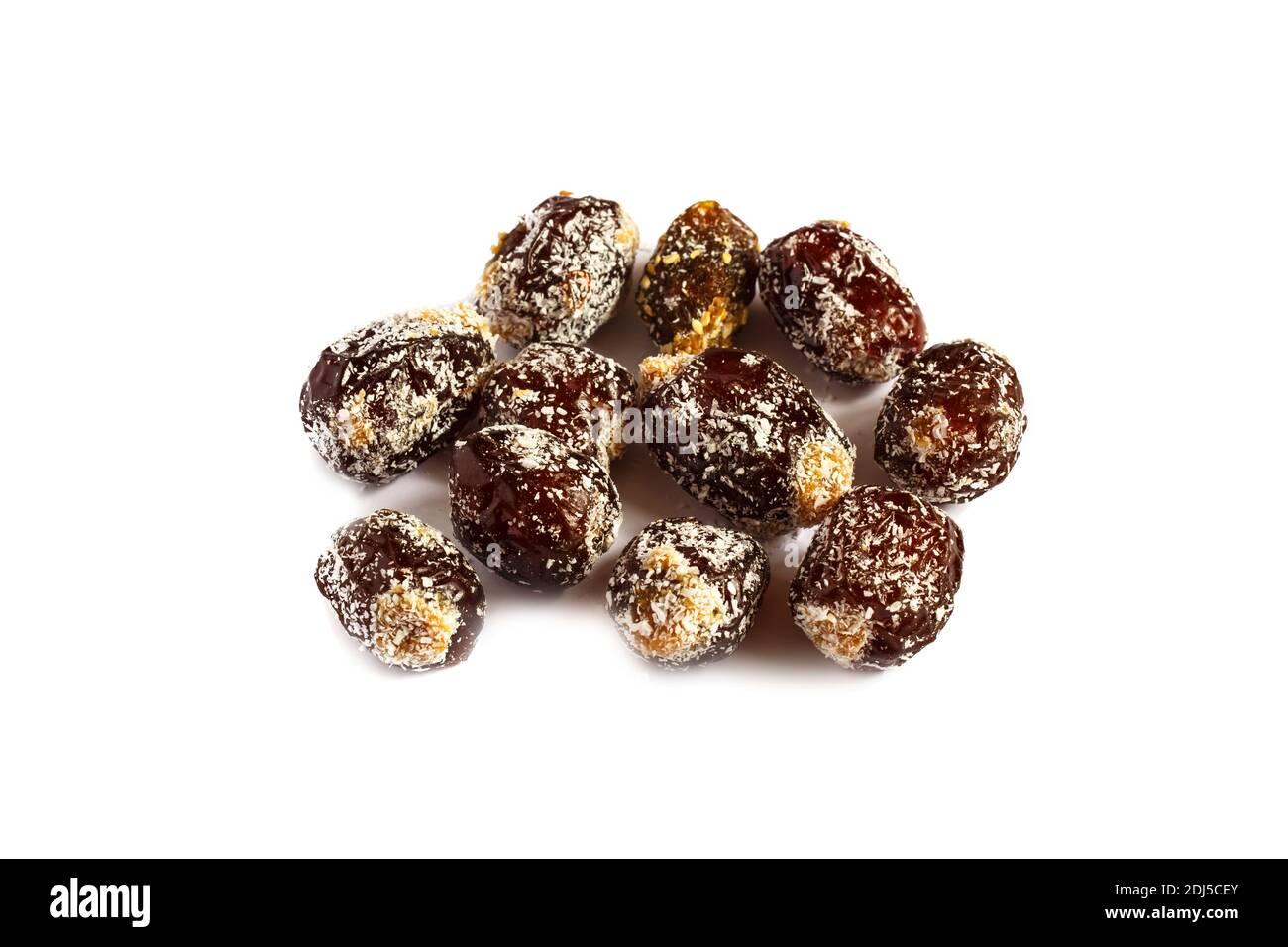 Dattes piquées isolées sur fond blanc. Dattes remplies de beurre d'arachide et parsemées de flocons de noix de coco Banque D'Images