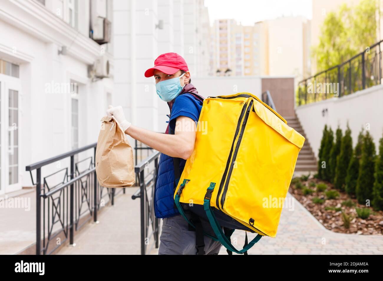 Portrait of a smiling man standing livraison avec sac à dos thermo jaune pour la livraison de nourriture dans la rue en plein air Banque D'Images