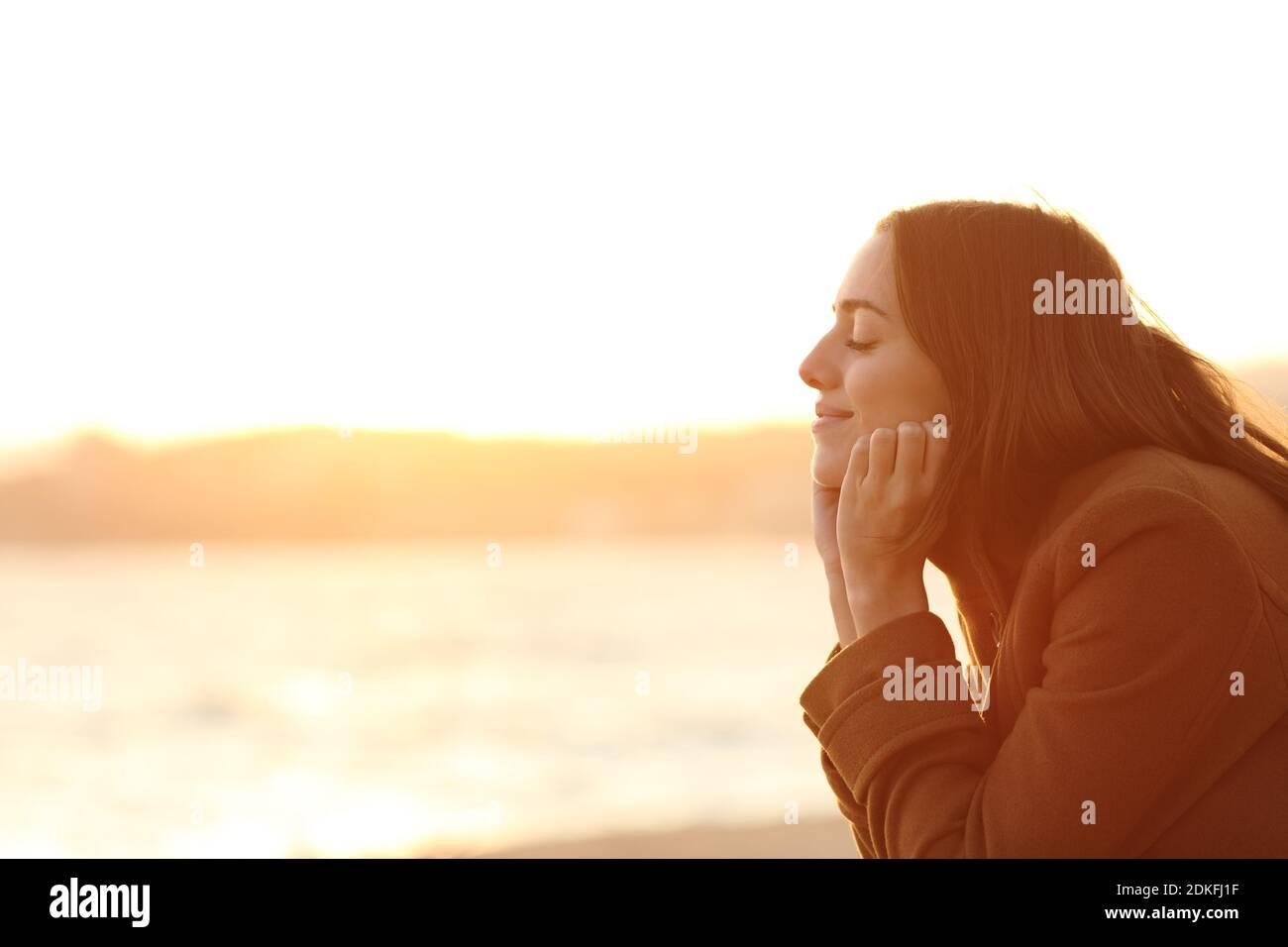 Profil d'une femme avec les yeux fermés au coucher du soleil relaxant l'esprit sur la plage en hiver Banque D'Images