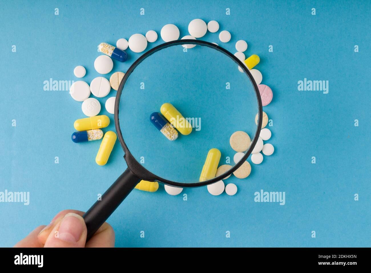 main femelle tient une loupe sur les pilules, fond bleu . Concept de fakes de médicaments et de qualité des substances médicinales Banque D'Images