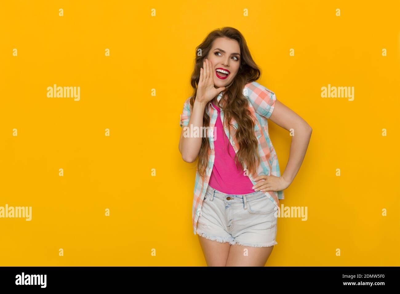 Une jeune femme heureuse en chemise de bûcheron sans bouton tient la main sur le menton, regarde loin et crie. Trois quarts de long de studio tourné sur fond jaune Banque D'Images