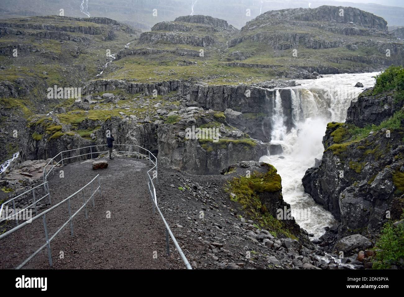 Un homme portant des mains noires se tient derrière des rampes dans la zone d'observation de Nykurhylsfoss (Sveinsstekksfoss) près de Djupivogur dans les Eastfjords d'Islande. Banque D'Images