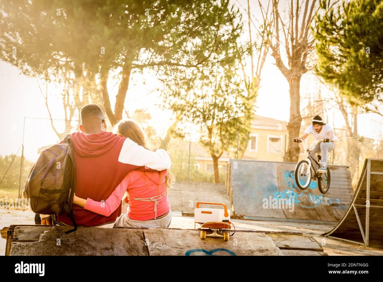 Vue arrière du jeune couple assis au parc Skateboard au coucher du soleil Banque D'Images