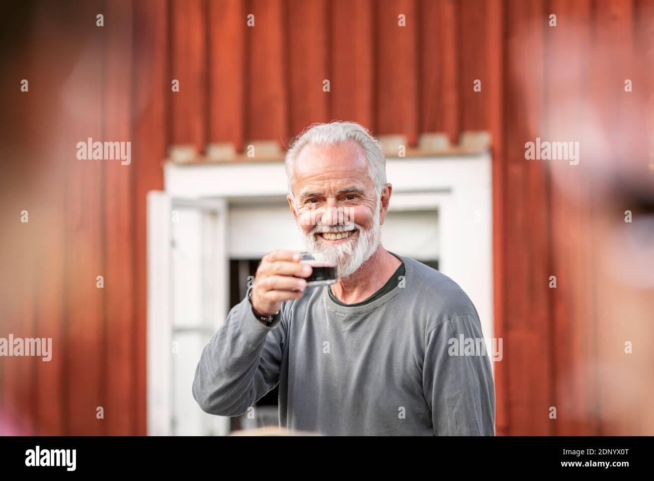 Homme souriant ayant du vin rouge Banque D'Images