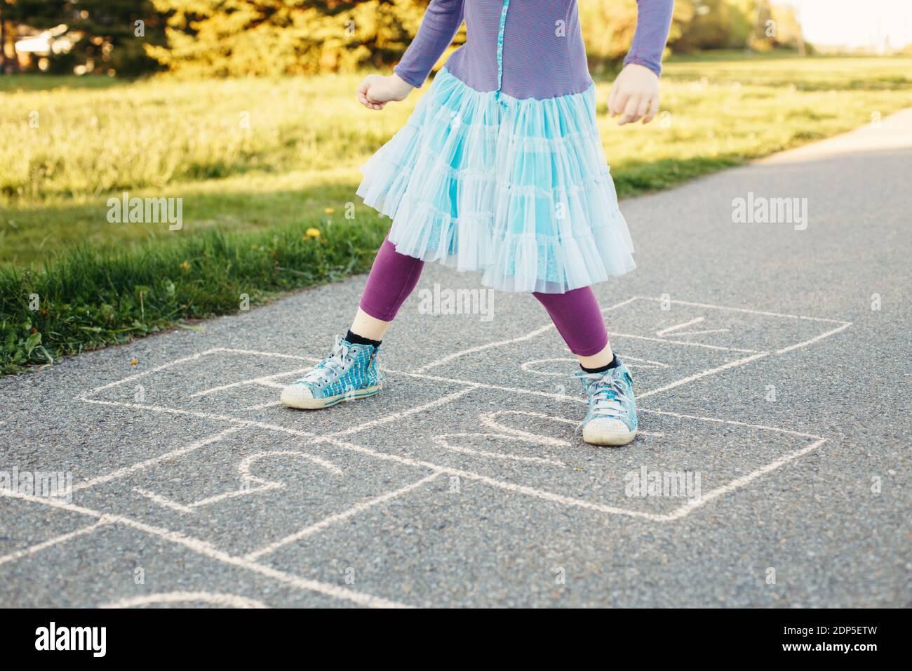 Gros plan de l'enfant fille jouant saut hopscotch en plein air. Jeu d'activités amusant pour les enfants sur l'aire de jeux à l'extérieur. Sports de rue de cour d'été pour les enfants Banque D'Images