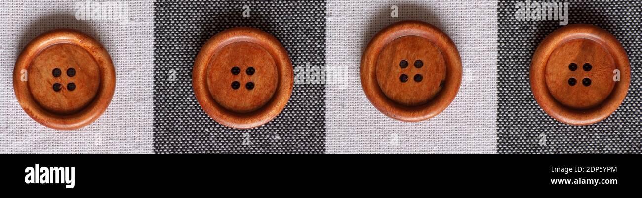 Boutons ronds de couture marron en bois isolés sur fond textile. Vue de dessus . Gros plan. Macro. Banque D'Images