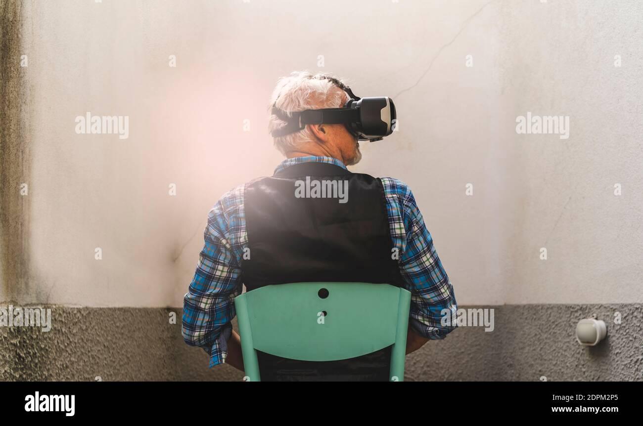 Vue arrière de l'homme senior regardant à travers le simulateur de réalité virtuelle tout en étant assis sur la chaise Banque D'Images