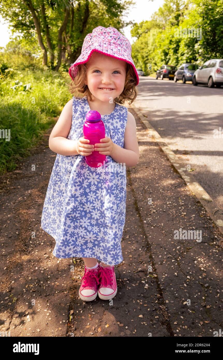 Joyeux sourire jeune fille de deux ans tenant de l'eau rechargeable bouteille à l'extérieur dans la rue Banque D'Images