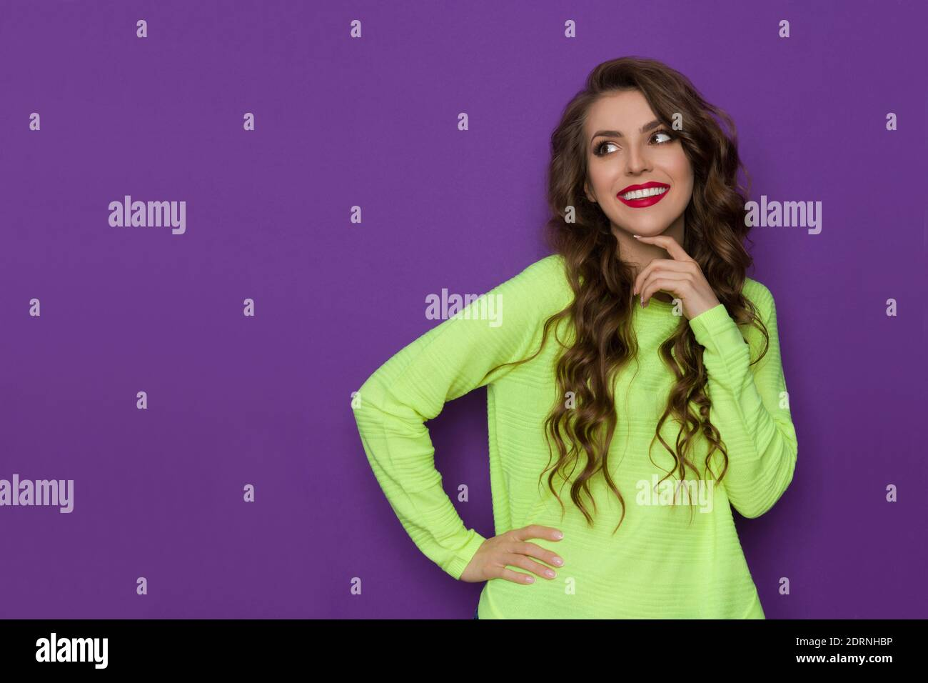 Une jeune femme heureuse dans un chandail vert citron vert fluo tient la main sur le menton, regardant le côté et souriant. Taille haute, prise en studio sur fond violet. Banque D'Images
