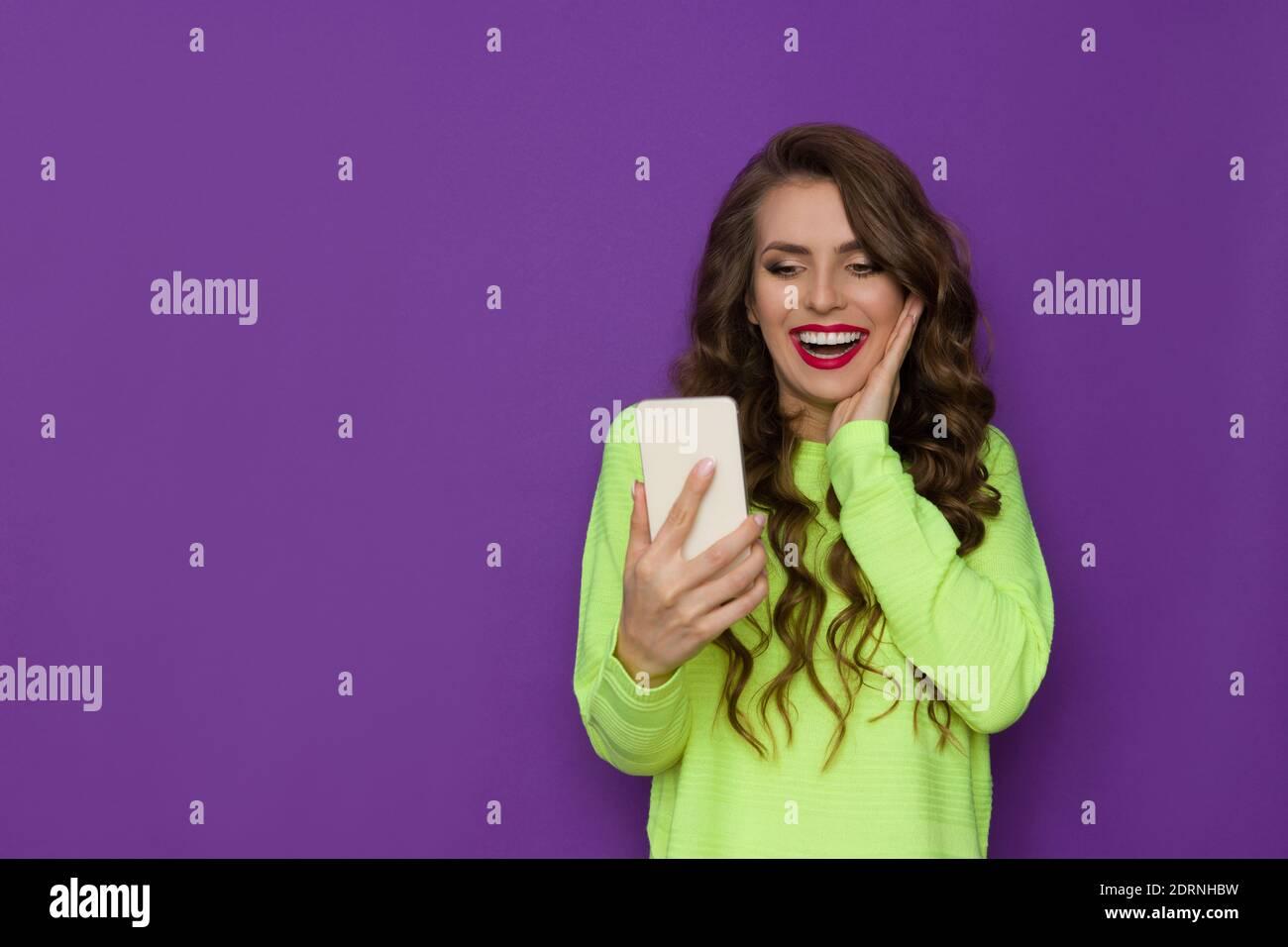 Belle jeune femme en vert fluo chandail tient le téléphone, le regardant et riant. Taille haute, prise en studio sur fond violet. Banque D'Images