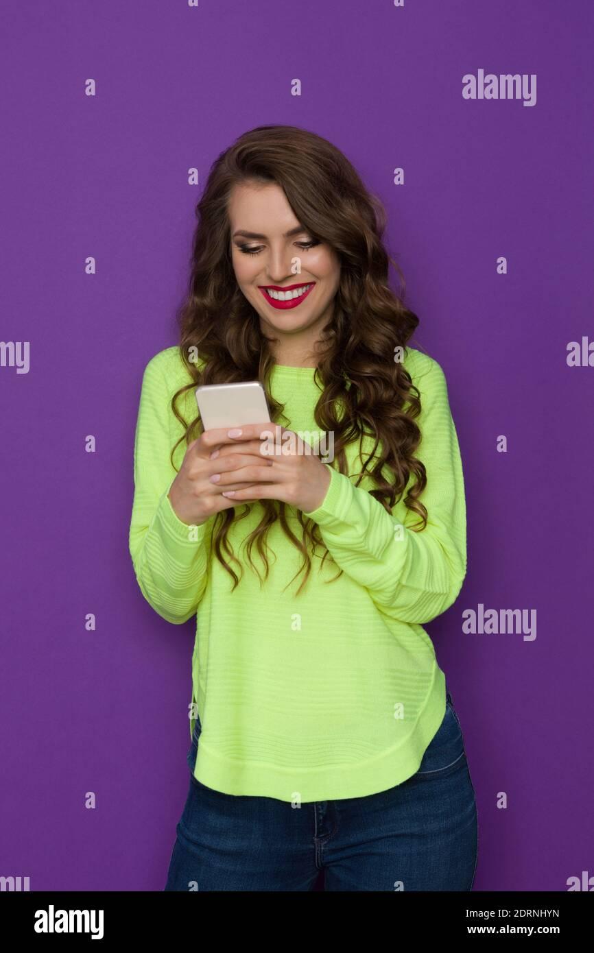 Une jeune femme heureuse en chandail vert néon tient le téléphone et écrit le message. Trois quarts de longueur en studio tourné sur fond violet. Banque D'Images