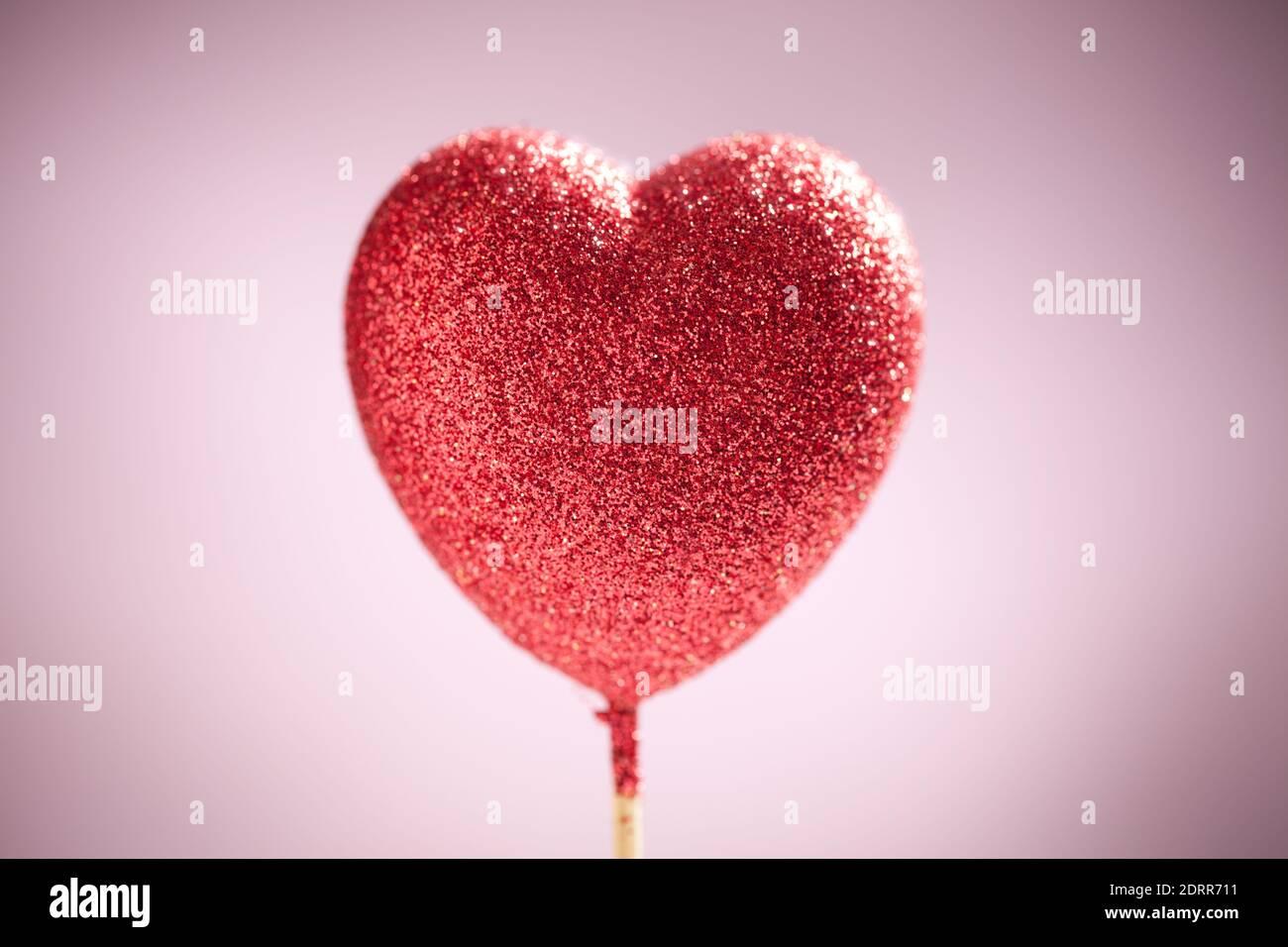 Gros plan sur un coeur scintillant sur fond rose flou. Ce fichier est nettoyé et retouché. Banque D'Images