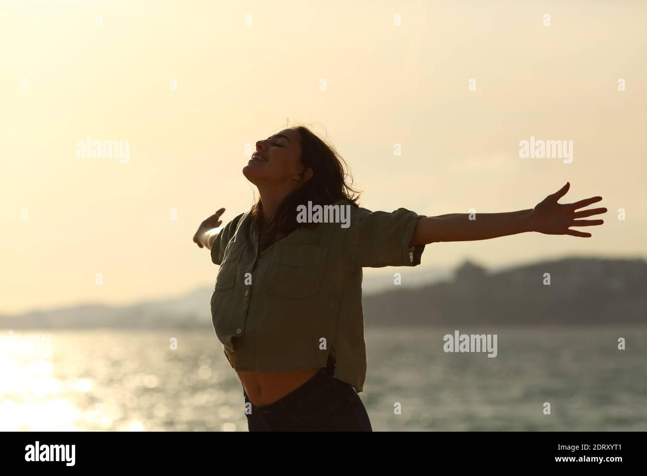 Silhouette d'une femme excitée qui s'étire les bras sur la plage au coucher du soleil Banque D'Images