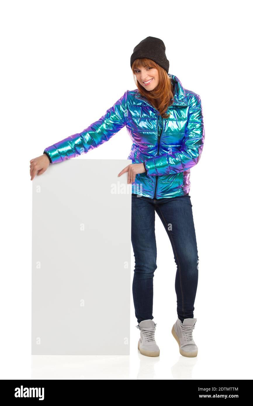 Jeune femme en blouson en duvet, casquette d'hiver, jeans et baskets, pose un écriteau blanc et sourit. Prise de vue en studio sur toute la longueur isolée sur Banque D'Images
