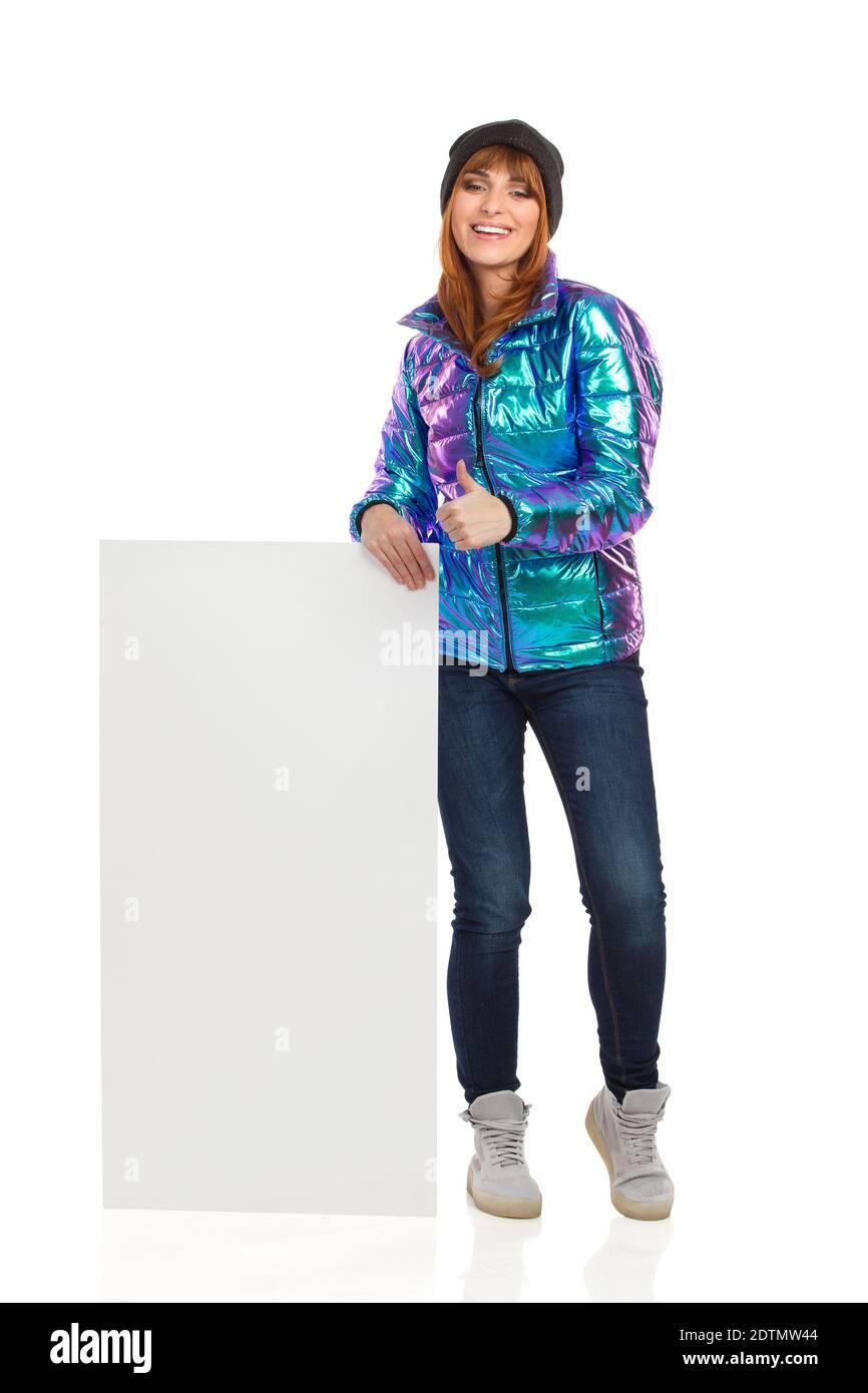 La jeune femme en veste duvet, casquette d'hiver, jeans et baskets est près de l'étiquette blanche, montrant le pouce vers le haut et souriant. Complet le Banque D'Images