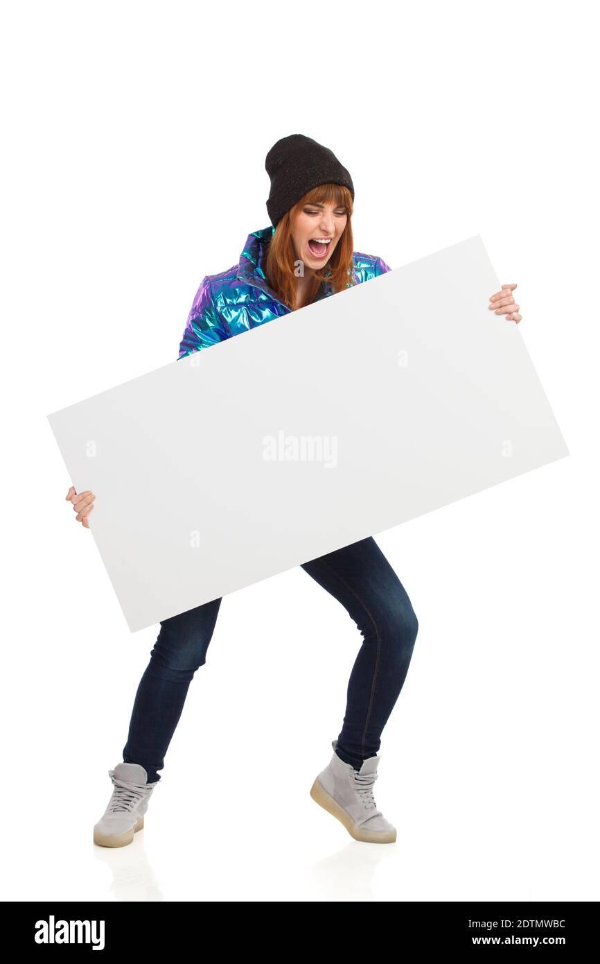 Crier une jeune femme dans des vêtements d'hiver tient une bannière blanche. Prise de vue en studio sur toute la longueur isolée sur blanc. Banque D'Images