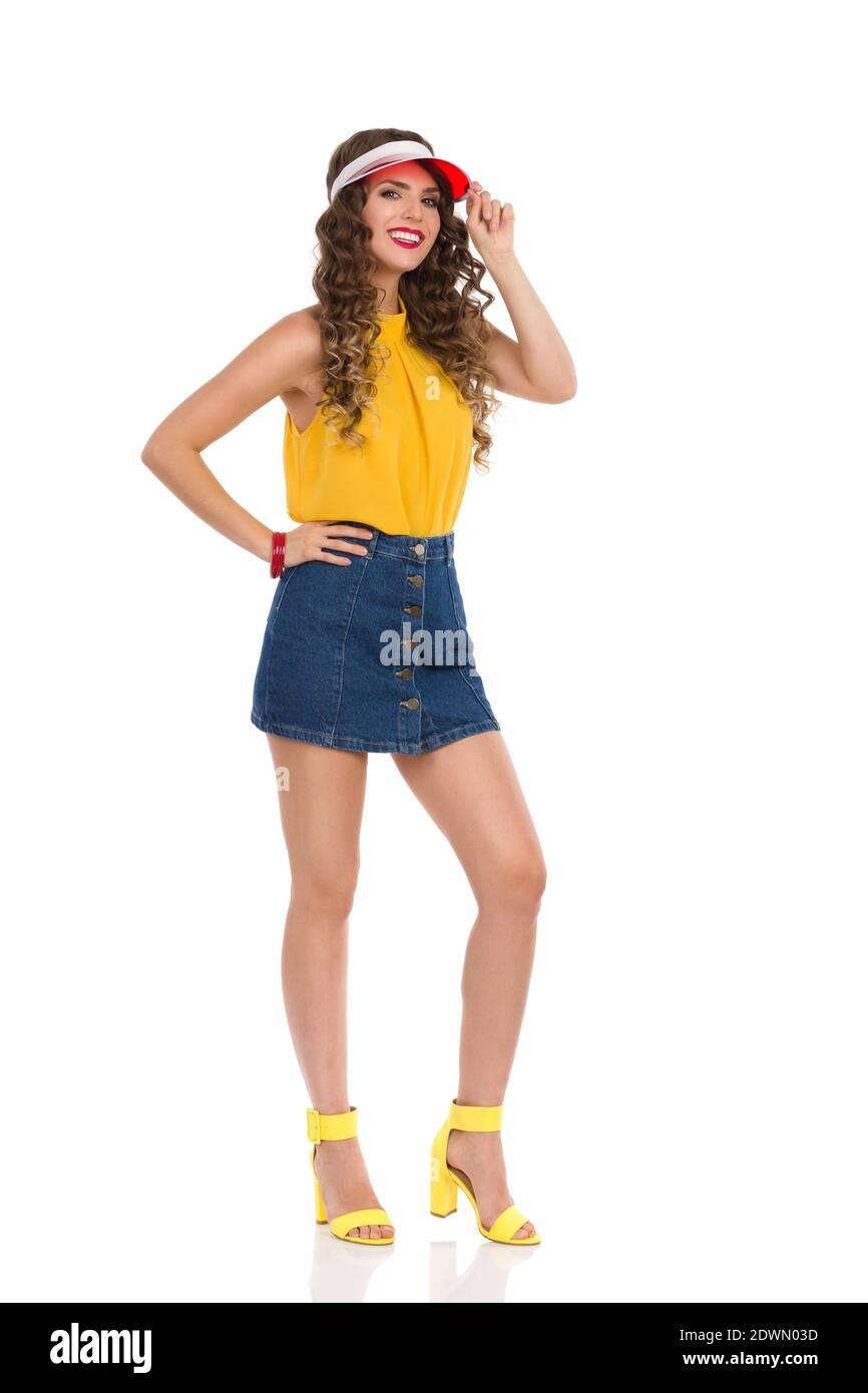 Le modèle de mode souriant est posé en Jean mini jupe, haut jaune, hauts talons sanals et chapeau de pare-soleil rouge. Prise de vue en studio sur toute la longueur isolée sur blanc. Banque D'Images