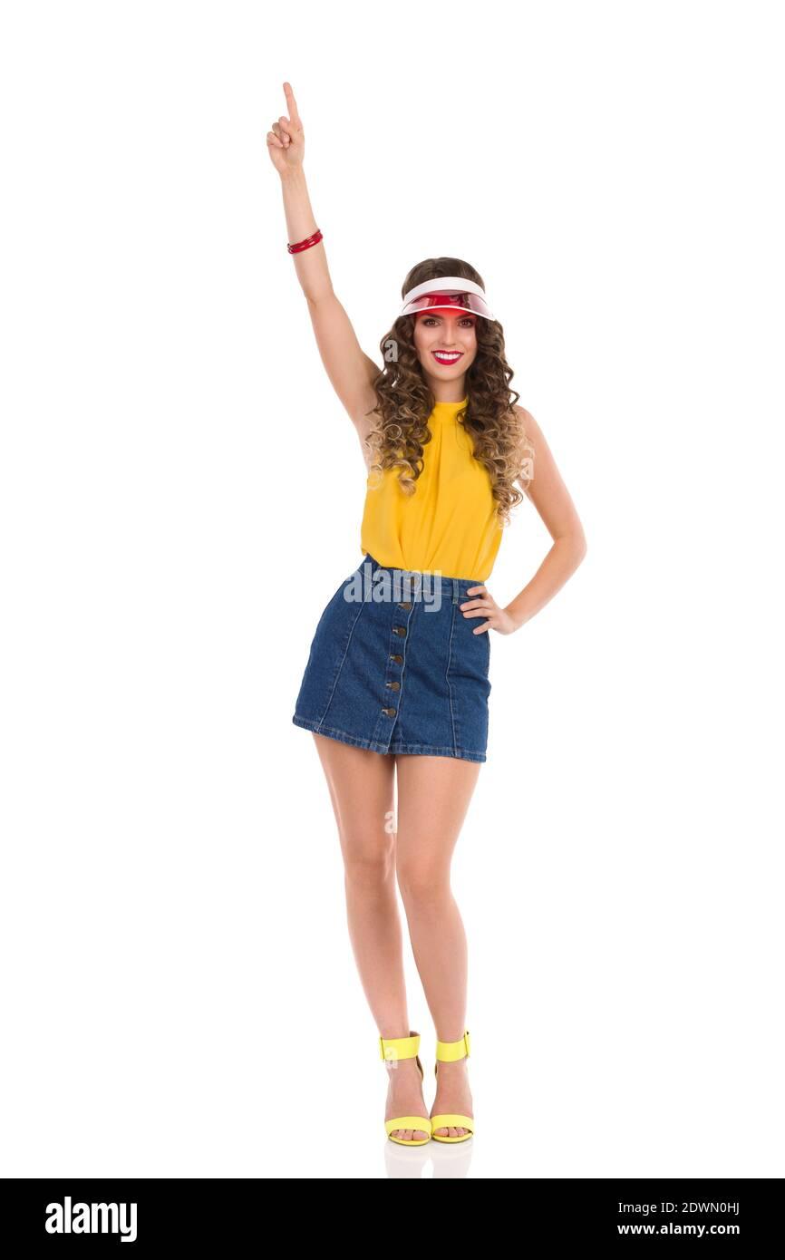 Modèle de mode souriant avec talons hauts sandales, Jean mini jupe, haut jaune et pare-soleil rouge est debout avec le bras relevé et pointant vers le haut. Vue avant. F Banque D'Images