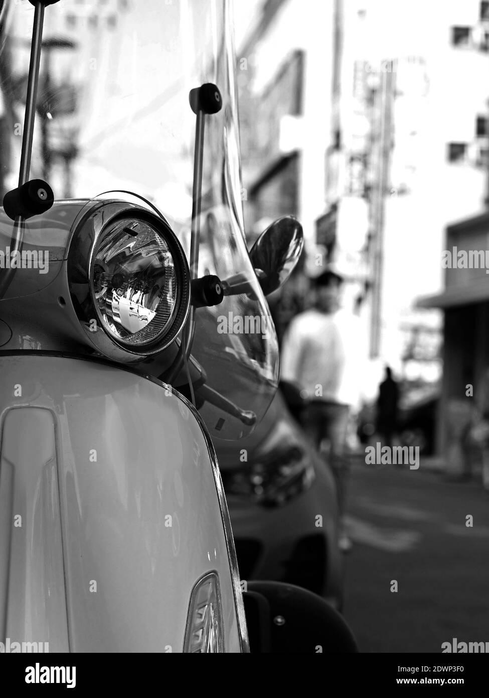 Détail des phares avant du stationnement de Scooter italien classique sur la rue urbaine. Mise au point sélectionnée. Banque D'Images