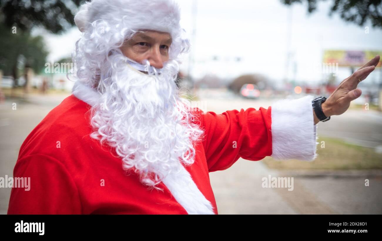 Bossier City, Louisiane, États-Unis. 23 décembre 2020. Le lieutenant-colonel Mark Geer de la U.S. Air Force, directeur du personnel de la 2e Escadre Bomb, célèbre l'esprit des fêtes en portant un costume de Santa tout en agitant les passants à la porte de la base aérienne de Barksdale le 23 décembre 2020 à Bossier City, en Louisiane. Credit: Planetpix/Alamy Live News Banque D'Images