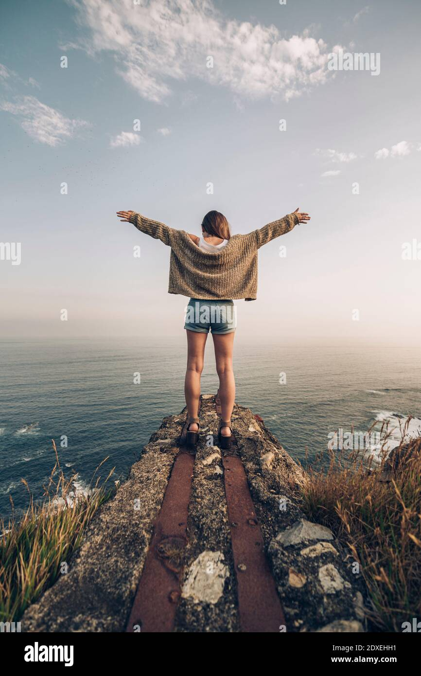 Jeune femme debout avec les bras étirés contre le ciel Banque D'Images