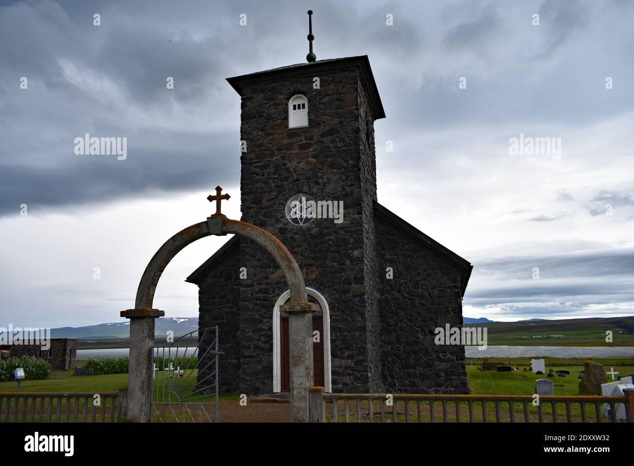 Église de Thingeyrar, ÉGLISE en pierre du XIXe siècle dans le nord de l'Islande. Une porte voûtée avec une croix mène au petit bâtiment noir par une journée. Banque D'Images