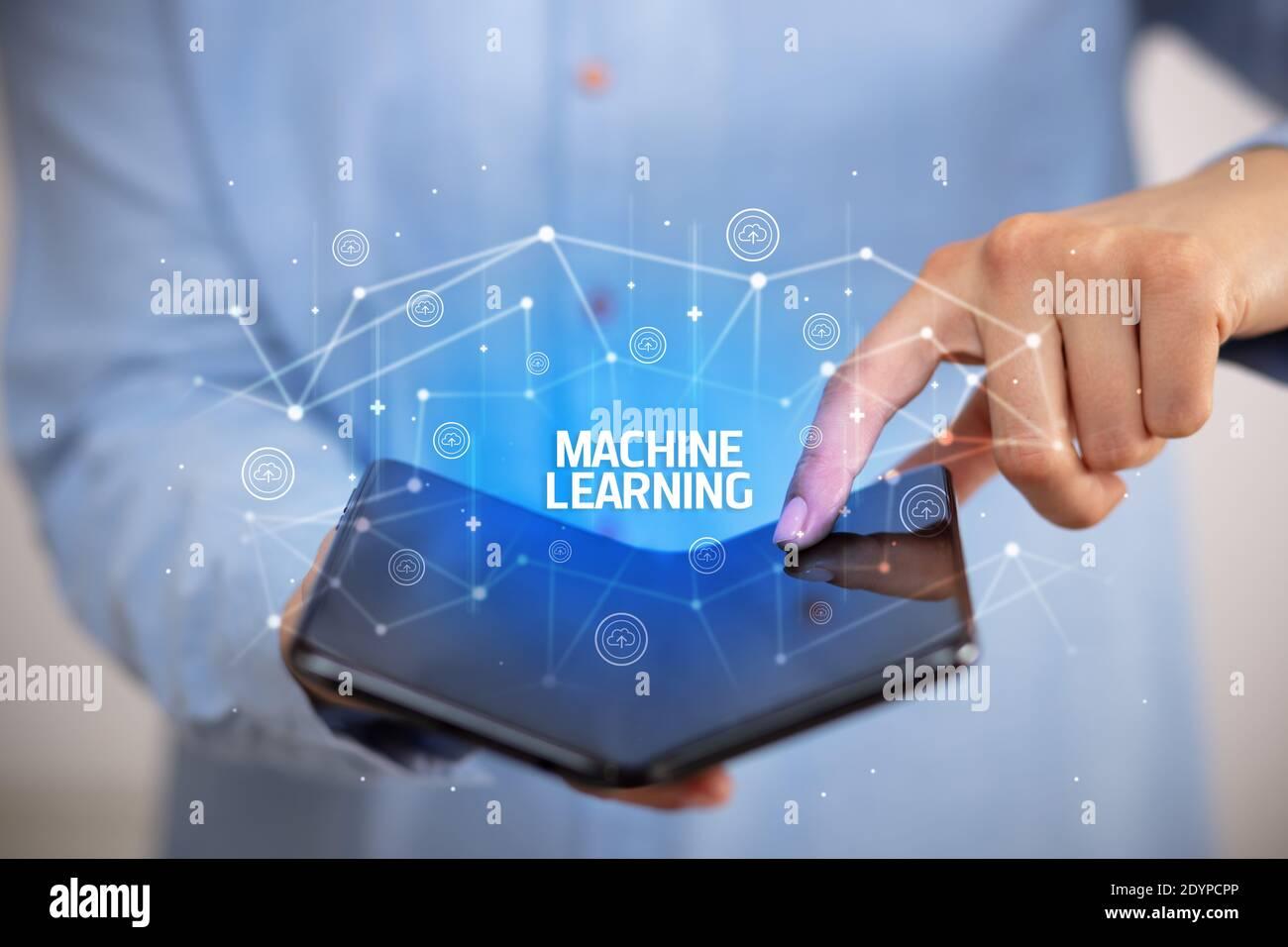 Businessman holding a smartphone pliable avec l'apprentissage automatique de l'inscription, la nouvelle technologie concept Banque D'Images